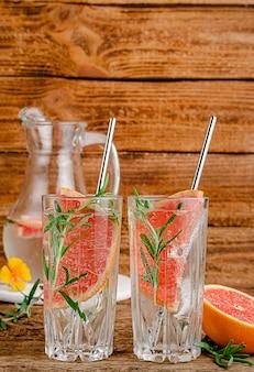 Gegoten water met grapefruit en rozemarijn op houten. verticaal