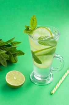 Gegoten water of koude limonade met limoen, ijs en munt in het glas op de groene achtergrond. locatie verticaal. kopieer ruimte.