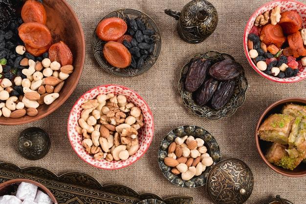 Gegraveerde metaal; koperen en keramische kom met gedroogde vruchten en noten op jute tafellaken