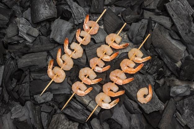 Gegrild eten. houtskoolspiesjes garnalen. gegrild eten. biologische gezonde voeding. plat leggen