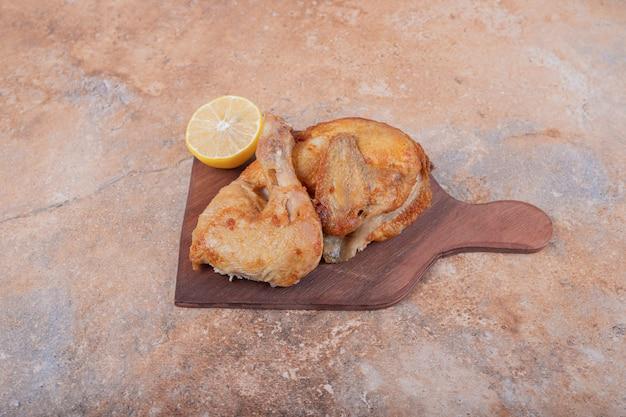 Gegrild kippenvlees met citroen op een houten schotel