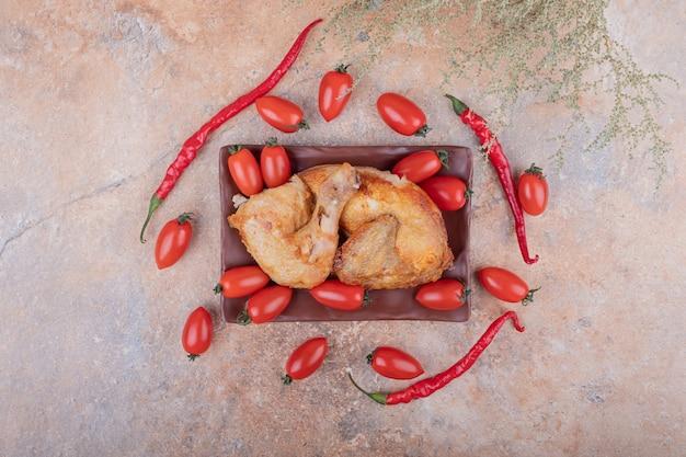 Gegrild kippenvlees met roodgloeiende chilipepers en kerstomaatjes