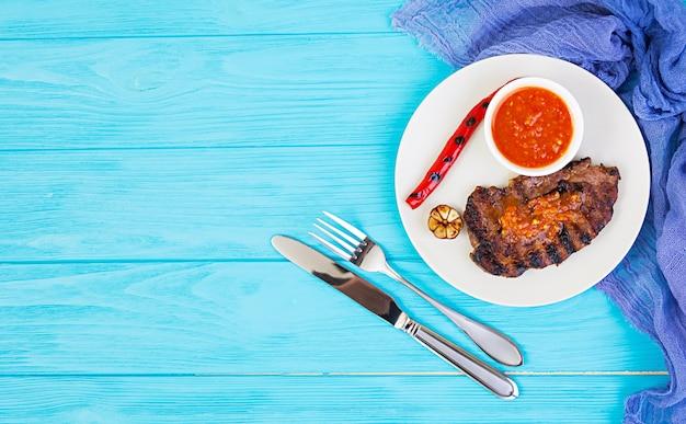 Gegrild sappig varkensvleeslapje vlees op houten lijst. bovenaanzicht