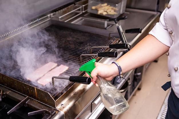 Gegrild spek door chef-kok in keukenrestaurant. heerlijke snelle keuken