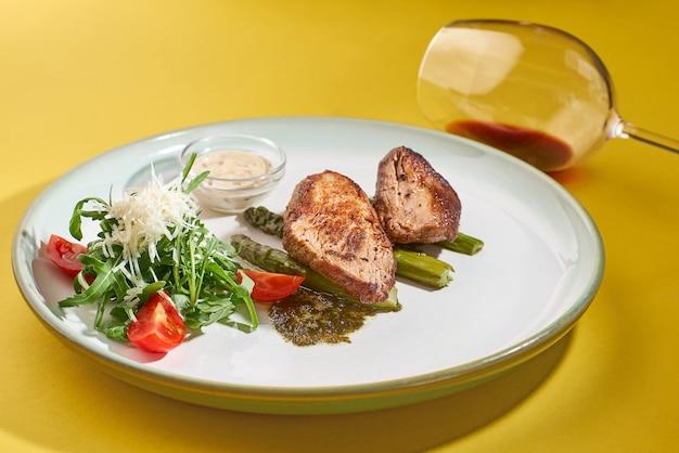 Gegrild varkensvlees met verse groentensalade en rode wijn op een gele muur