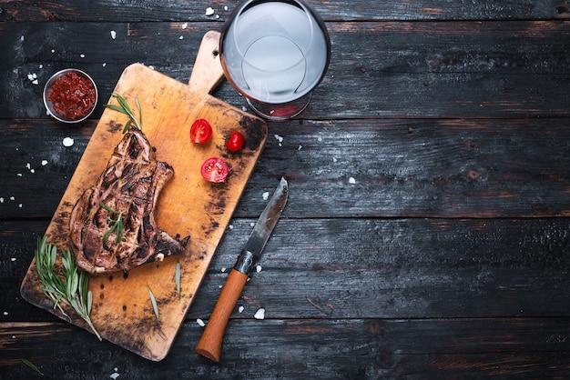 Gegrild vlees, een restaurantmenu, een glas droge rode wijn. geurige specerijen en kruiden.