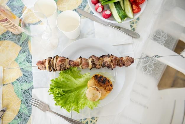Gegrild vlees en ui op tafel met groenten