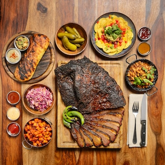 Gegrild vlees geserveerd met salades, chips en sauzen op houten bureau