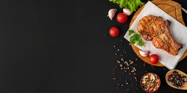 Gegrild vlees kopie ruimte, donkere ondergrond, kruiden, sla, tomaat, zwarte kruiden in de houten lepels