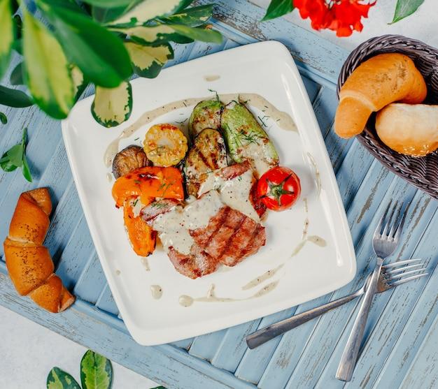 Gegrild vlees met gegrilde groenten, rijst en tomaat.