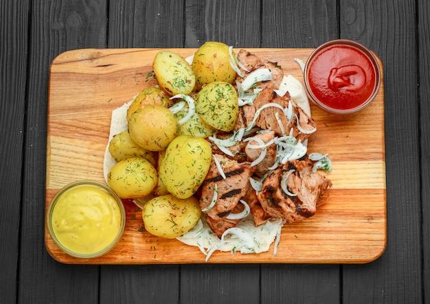 Gegrild vlees met gekookte aardappelen en groenten