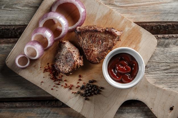Gegrild vlees met kruiden en tomatensaus op een versleten houten achtergrond