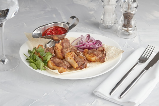 Gegrild vlees op een plaat, die in een restaurant, lichte achtergrond dient Premium Foto