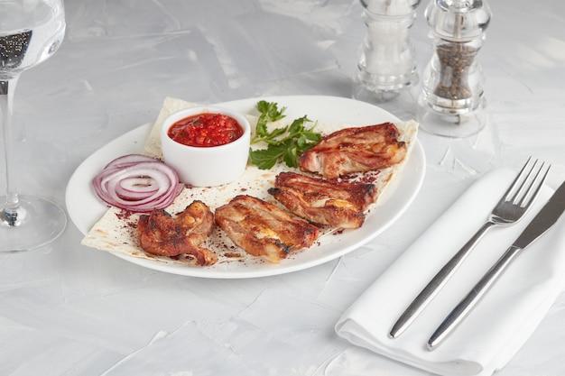 Gegrild vlees op een plaat, die in een restaurant, lichte achtergrond dient