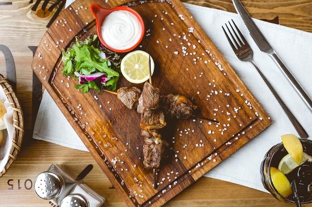 Gegrild vlees op houten stokken zout zure room citroen radijs sla bovenaanzicht