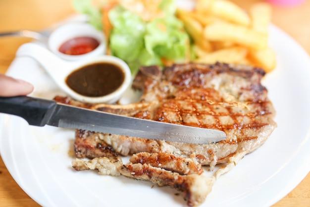 Gegrild vlees, porkchops steak met pepersaus en salade.