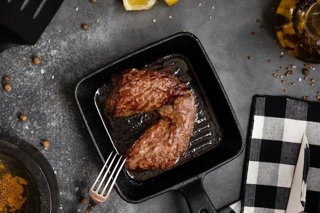 Gegrild vlees steak machete met zout en peper op leisteen bord zwart, bovenaanzicht