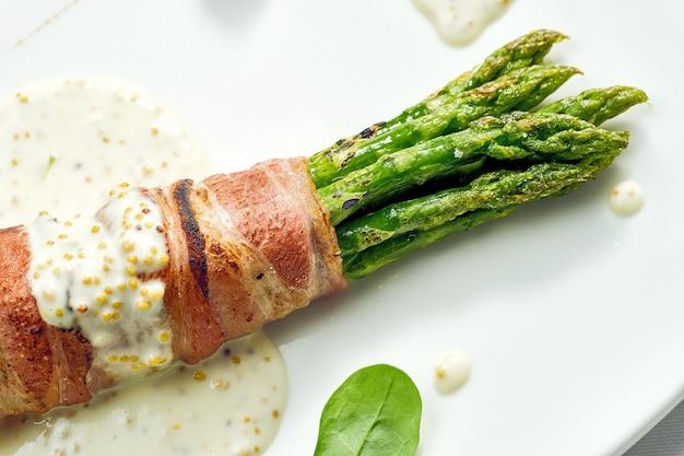 Gegrilde asperges met spek en mosterdsaus in een witte plaat. geïsoleerd op een witte ondergrond.