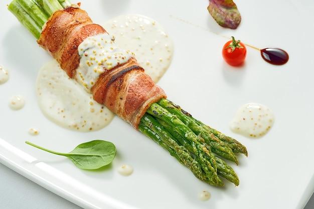 Gegrilde asperges met spek en mosterdsaus in een witte plaat. geïsoleerd op gery oppervlak.