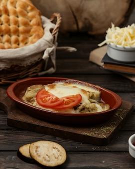 Gegrilde aubergine gegarneerd met gesmolten kaas in aardewerk pan