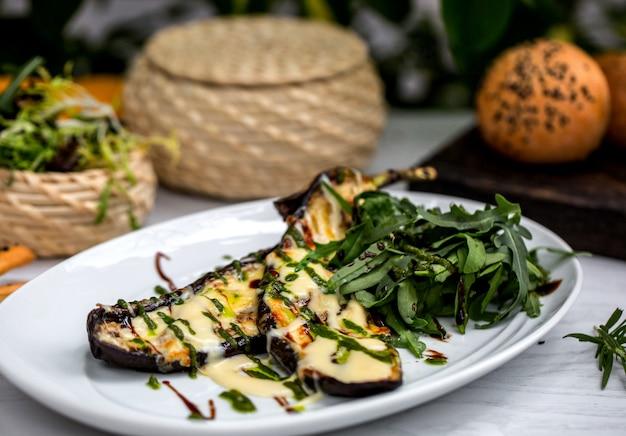 Gegrilde aubergine plakjes gegarneerd met gesmolten kaas en dragon