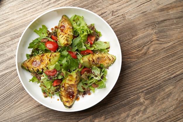 Gegrilde avocado met amarantzaden. gezonde veganistische lunchkom. avocadosalade met verse bladeren en groente