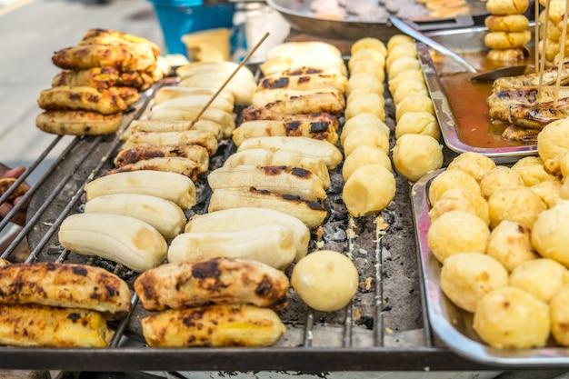 Gegrilde banaan en zoete aardappel te koop bij een lokale markt in bangkok, thailand.