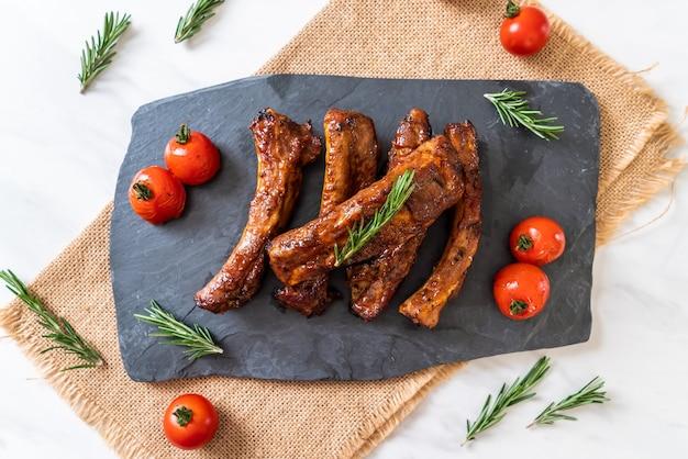 Gegrilde barbecue ribben varkensvlees met rozemarijn en tomaten