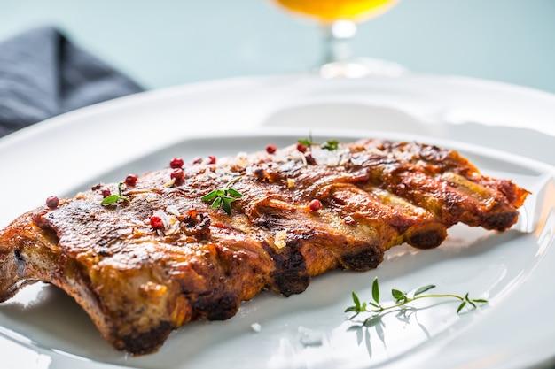 Gegrilde barbecue varkensribbetjes in een witte plaat als menu in pub of restaurant.