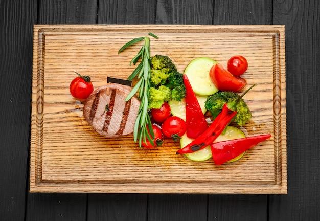 Gegrilde bbq steak met aardappel kubus en tomaten.