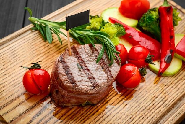 Gegrilde bbq steak met aardappelblokje en tomaten.