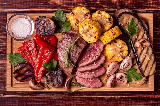 Gegrilde biefstuk en groenten op snijplank.