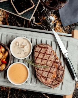 Gegrilde biefstuk geserveerd met champignonsaus en aardappelschotel