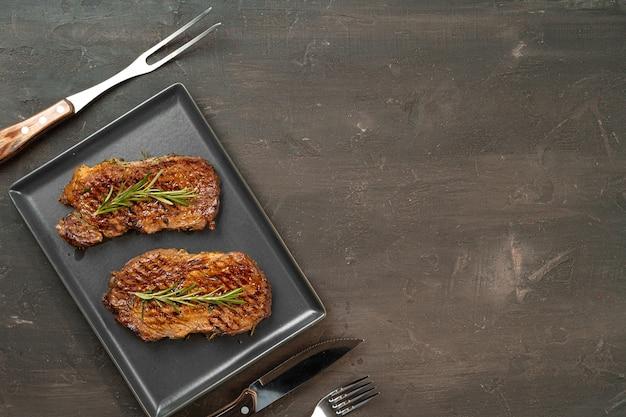 Gegrilde biefstuk geserveerd met rozemarijn op metalen dienblad, close-up