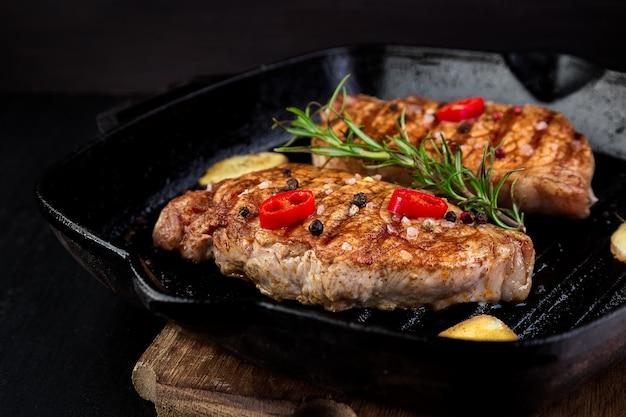 Gegrilde biefstuk in grillpan met rozemarijn, pepers en gember op houten bord.