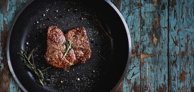 Gegrilde biefstuk in koekenpan op houtstructuur