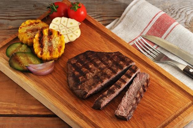 Gegrilde biefstuk, in stukjes gesneden, gegrilde groenten - courgette, maïs, ui, knoflook, kers