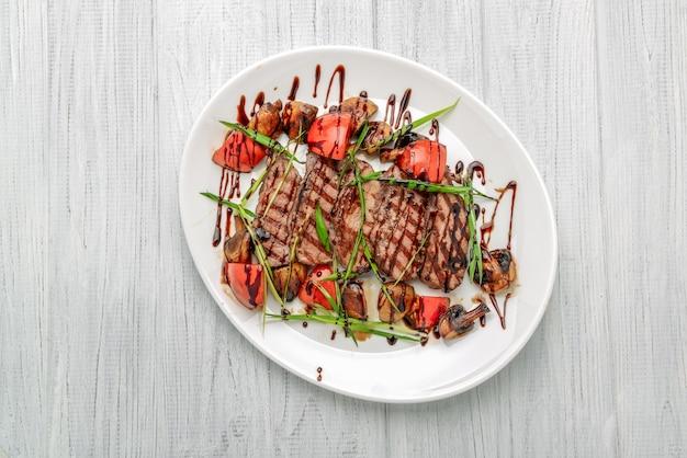 Gegrilde biefstuk met champignons en tomaten. concept voor gezonde voeding.