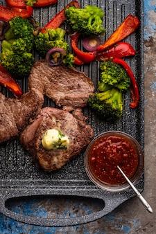 Gegrilde biefstuk met kruidenboter en groenten. vlees met gegrilde paprika, broccoli en uien.