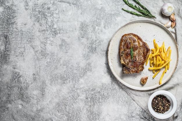 Gegrilde biefstuk op been met frietjes. grijze achtergrond. bovenaanzicht. ruimte voor tekst