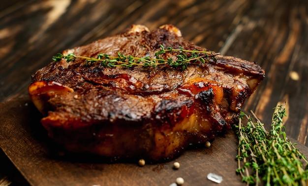 Gegrilde biefstuk op een snijplank met kruiden en citroen op een houten achtergrond