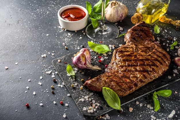 Gegrilde biefstuk van geroosterd vlees op zwarte achtergrond, met wijn, ketchupsaus, kruiden en specerijen