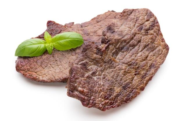 Gegrilde bio rundvleeslapjes vlees met geïsoleerde kruiden.