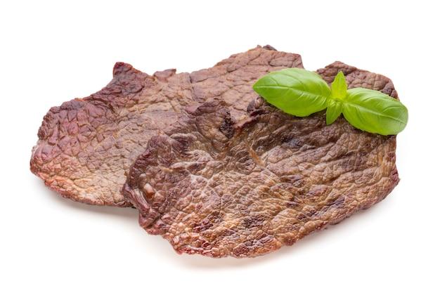 Gegrilde bio rundvleeslapjes vlees met kruiden die op wit worden geïsoleerd.