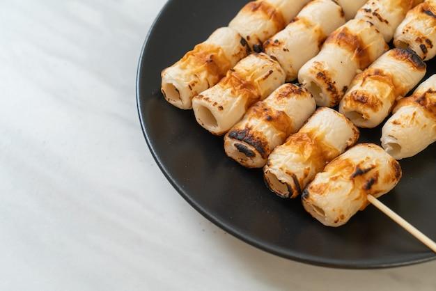 Gegrilde buisvormige vispasta cake of buisinktvis spies op bord