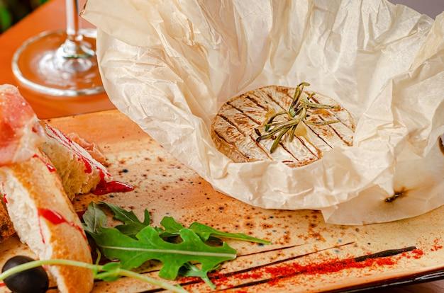 Gegrilde camembert-kaas met rozemarijn. franse keuken, restaurant serveren.