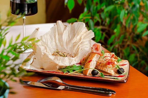 Gegrilde camembertkaas met stokbrood, ham en glas rode wijn. franse delicatesse concept.