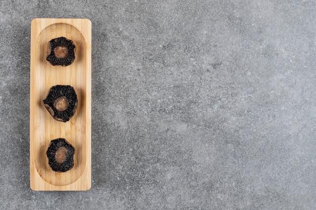 Gegrilde champignons op een houten bord over grijze ondergrond