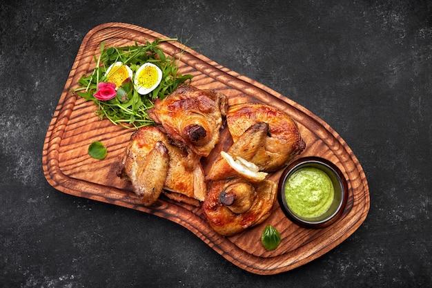 Gegrilde chick met kruiden en saus op een houten bord op een zwarte achtergrond