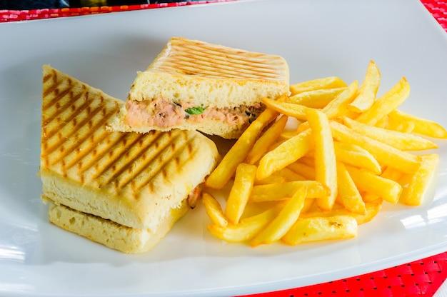 Gegrilde clubsandwich met frieten die op witte plaat worden geïsoleerd.